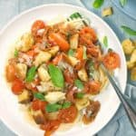 pasta with tomatoes and basil on a white plate