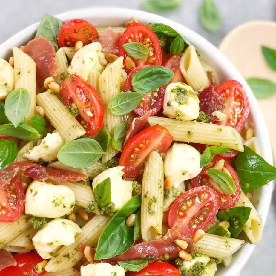 tomato basil mozzarella pasta salad in a white bowl