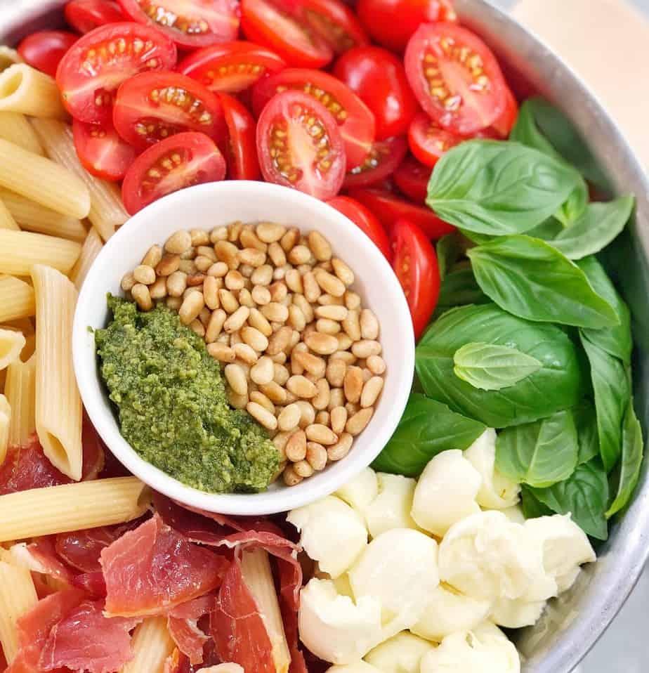 ingredients to make pesto mozzarella pasta in a silver bowl