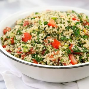 chopped tomato and parsley salad in a white bowl