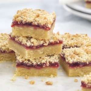 pieces of crumbly slice with raspberry jam on a white surface