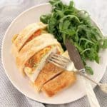 chicken breast with pastry on top with green salad on a while plate