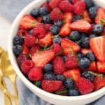 blue and red berries in a white bowl