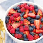 strawberries, blueberries, raspberries and mint slices in a white bowl