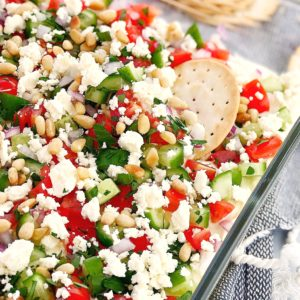 greek layered dip in a glass dish with crackers