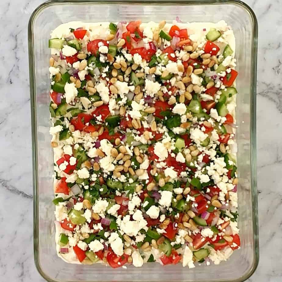 greek layered dip in a glass dish with tomato and cucumber on top