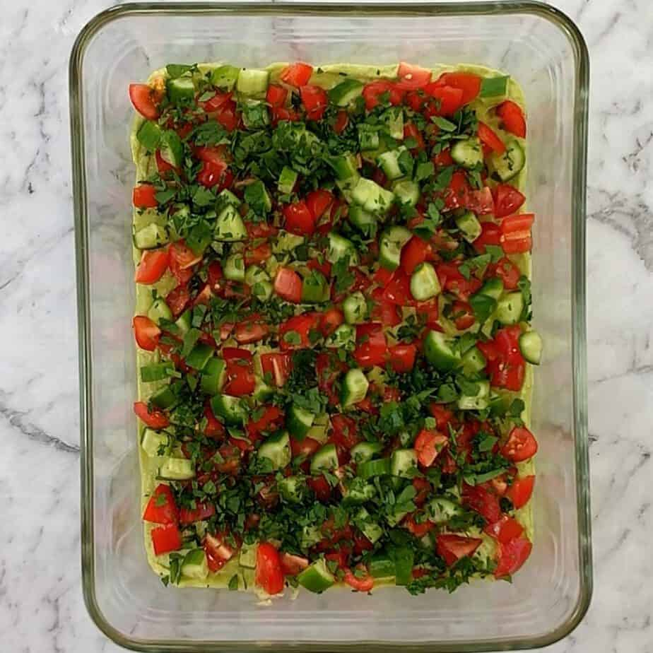 chopped parsley cucumber tomato on top of mashed layer of avocado in glass dish