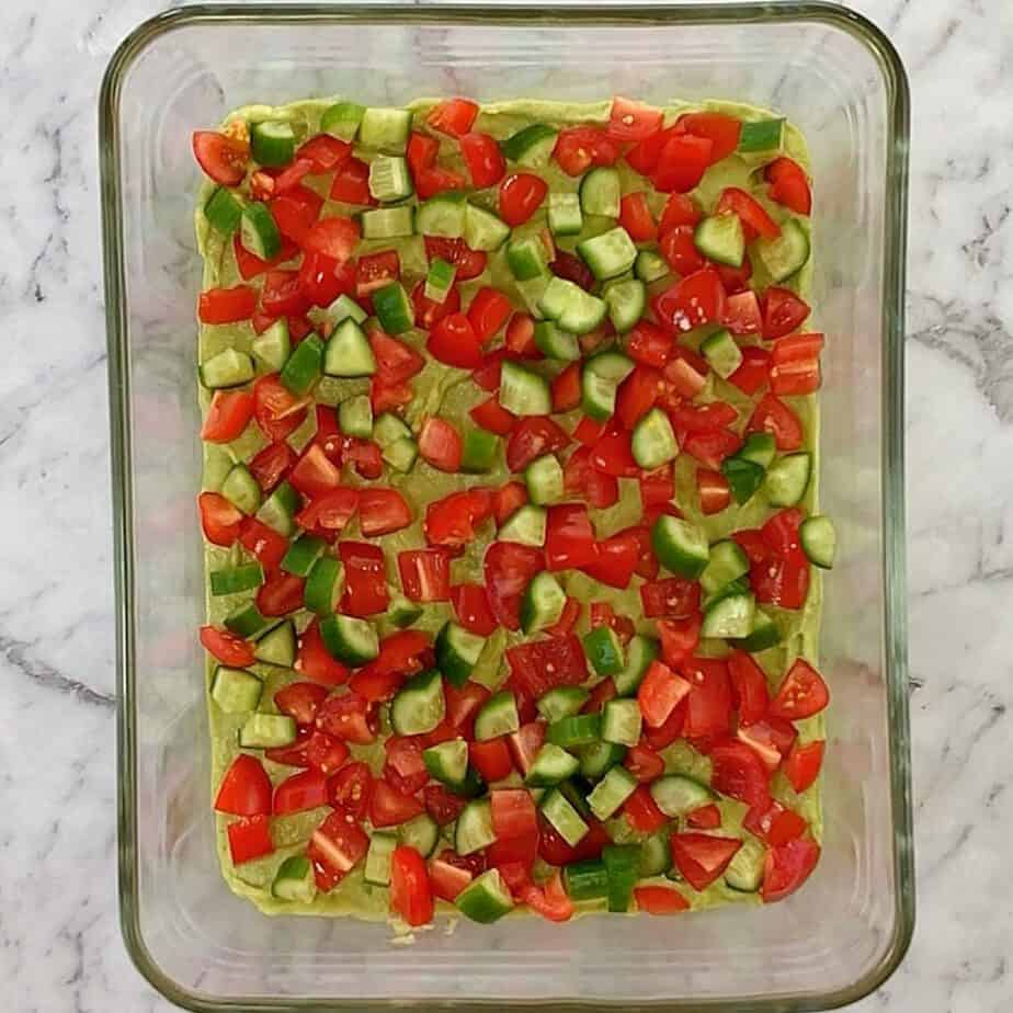 chopped cucumber and tomato on top of a layer of mashed avocado in a glass dish
