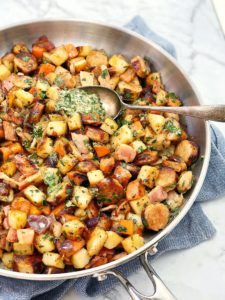 Chopped sausages and vegetables in a silver pan with herb sauce