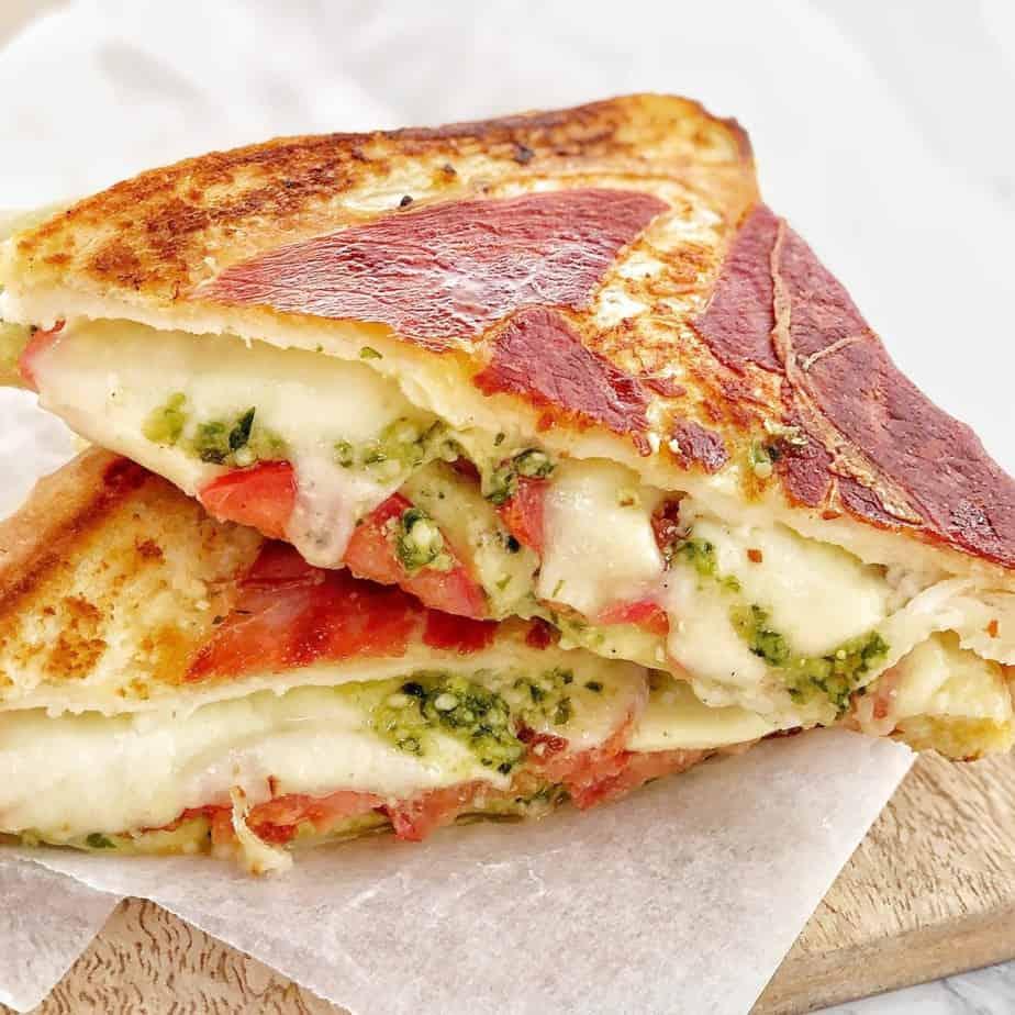 sandwith cheese tomato and pesto wrapped in prosciutto on a bread board