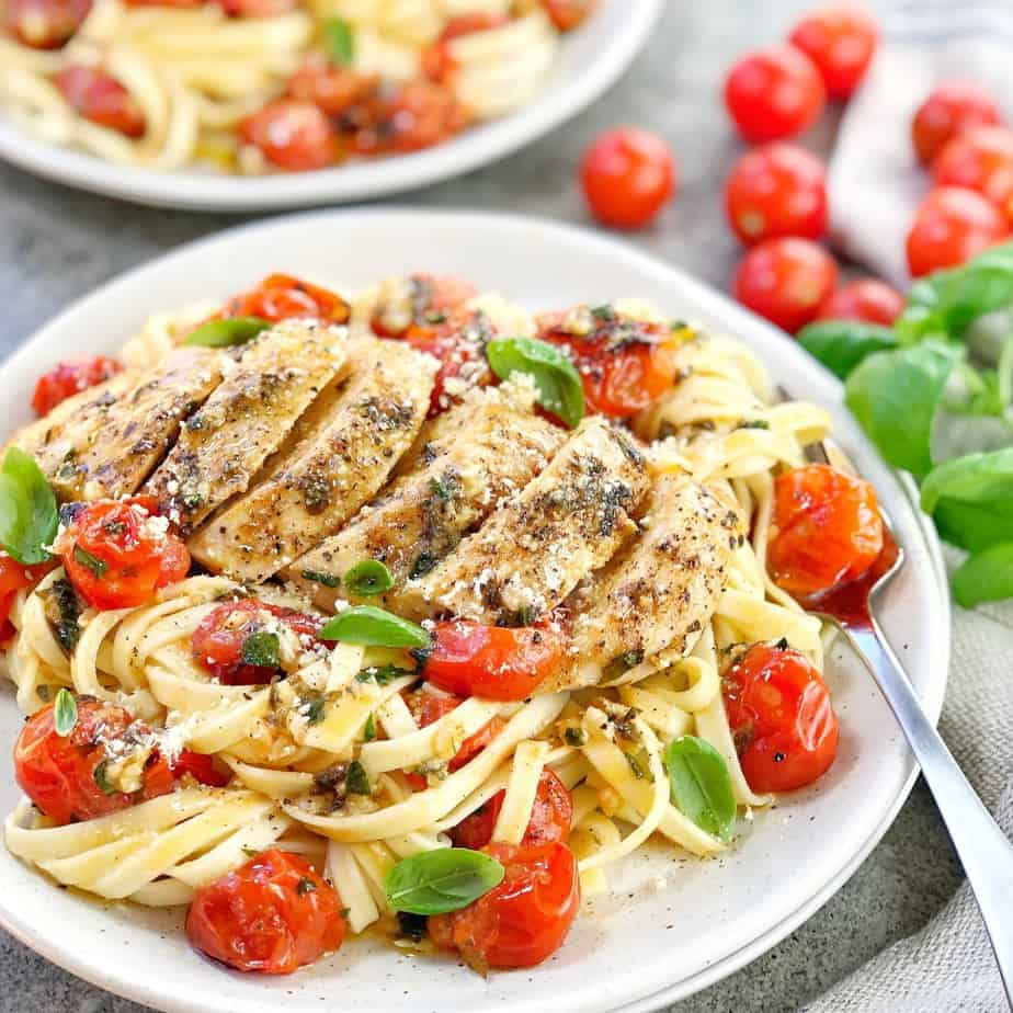chicken cherry tomato pasta on white plate with chicken breast and red cherry tomatoes on top