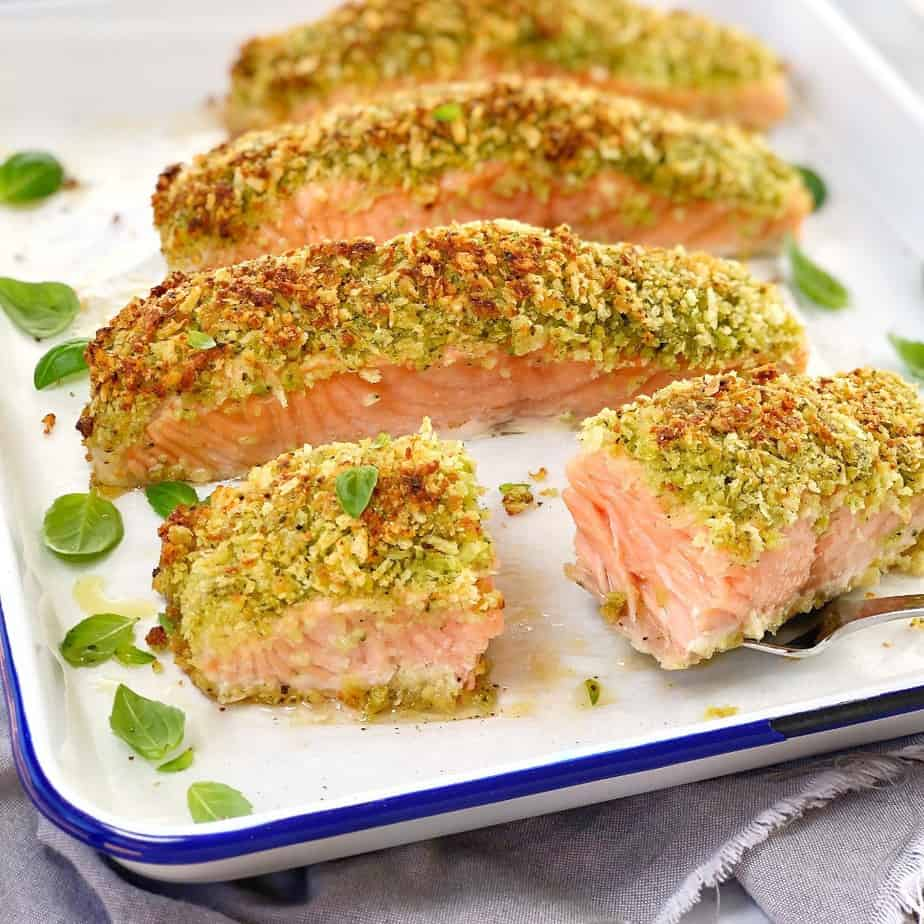 baked salmon fillets with pesto crust on a white baking tray