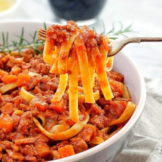 lamb ragu with pasta in a white bowl