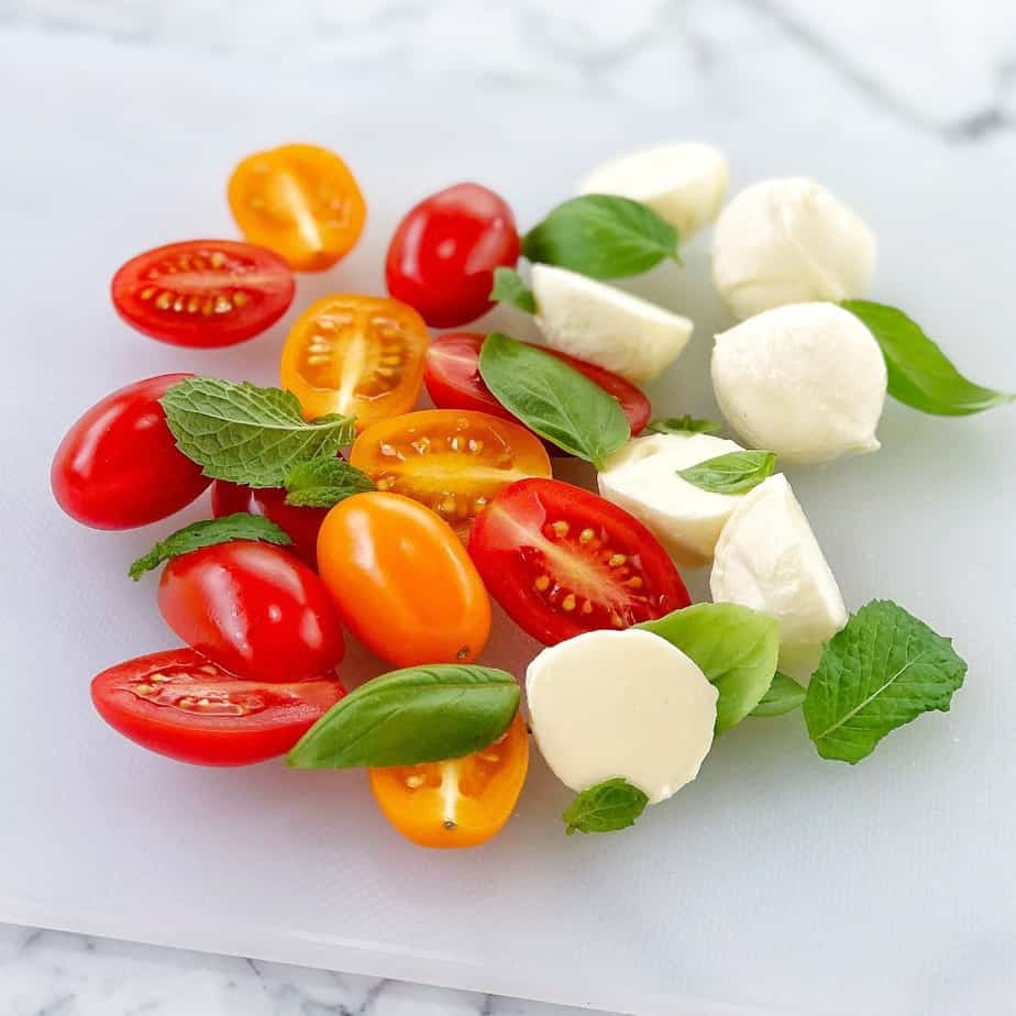 chopped tomatoes basil mint and bocconcini on a white cutting board