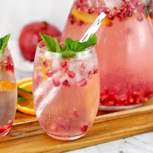 cocktail with pomegranate and mint in a glass on a board