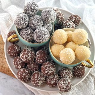 chocolate balls covered in coconut in cups on a white plate