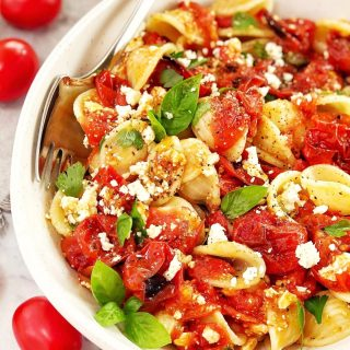 tomato and herb pasta in a white bowl