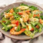 prawns sliced pears and green salad leaves on a grey plate