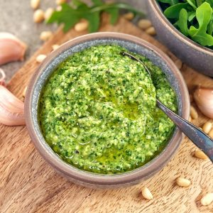green rocket pesto in a grey bowl on a wooden board