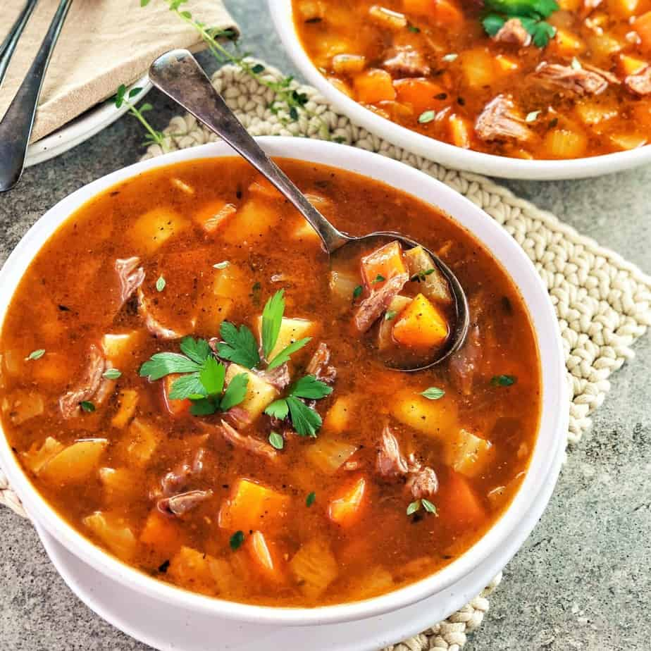 lamb and vegetable soup in a white bowl