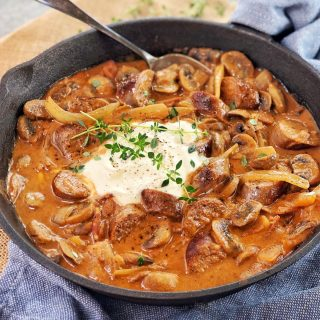 chopped sausages mushrooms and onions in a tomato sauce with sour cream on top in a black pan