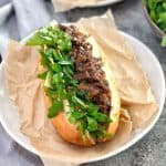 bread roll filled with lamb and gravy and salad on a white plate
