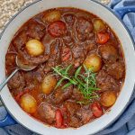 lamb and onion stew in a blue pot