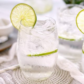 clear drink in a clear glass with a slice of lime on the side